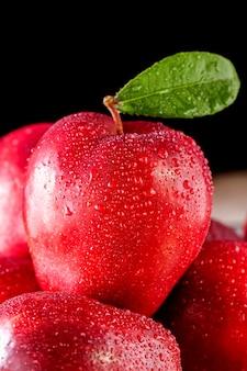 Czerwone jabłka z liśćmi na stole. widok z góry