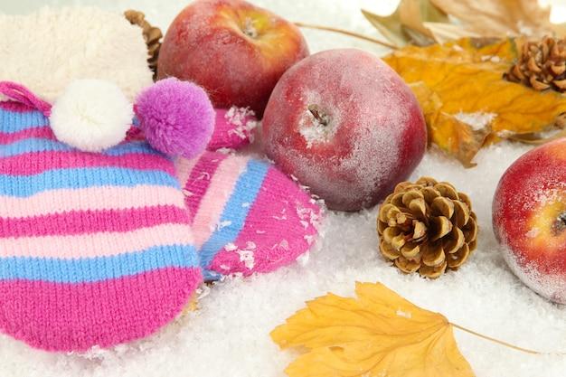 Czerwone jabłka z rękawiczkami w śniegu z bliska