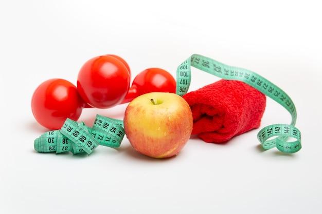 Czerwone jabłko i hantle z miarką biały