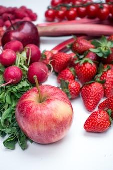 Czerwone jabłko i inne czerwone owoce i warzywa na białym tle