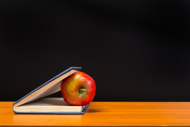Czerwone jabłko i stare książki na drewnianym blacie