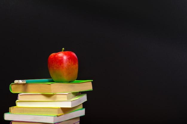 Czerwone jabłko i stare książki na drewnianym tabletop