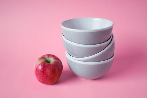 Czerwone jabłko i stos ceramicznych misek kuchennych