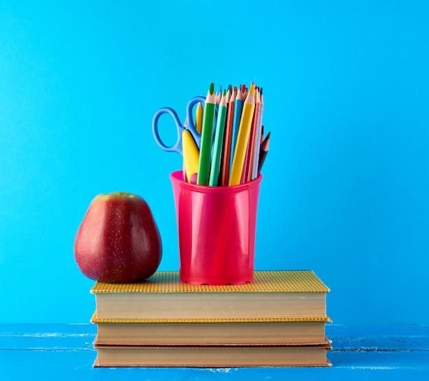 Czerwone jabłko i stos książek