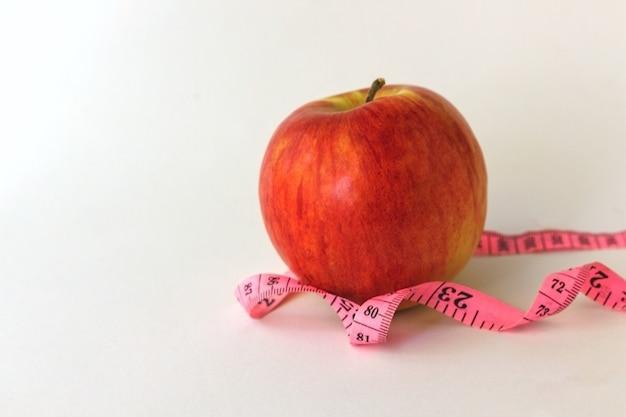 Czerwone jabłko i taśma miernicza na białym tle