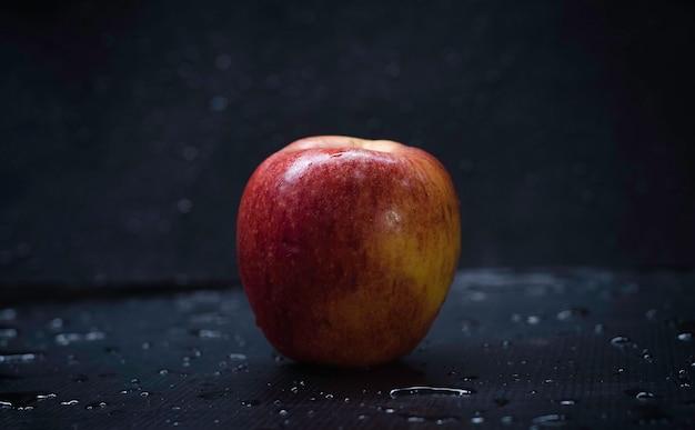 Czerwone jabłko kładzie mokre tło, pokazuje fakturę skórki i kształtu, rozmyte światło dookoła