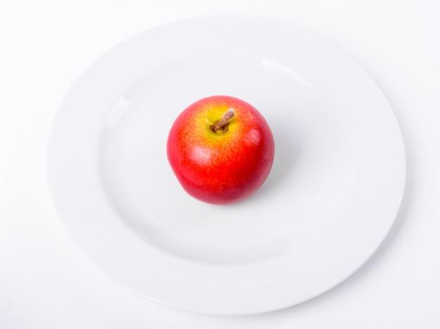 Czerwone jabłko na białym talerzu samodzielnie