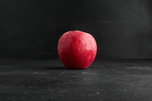 Czerwone jabłko na białym tle na czarnej powierzchni.