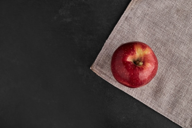 Czerwone jabłko na białym tle na ręcznik kuchenny.