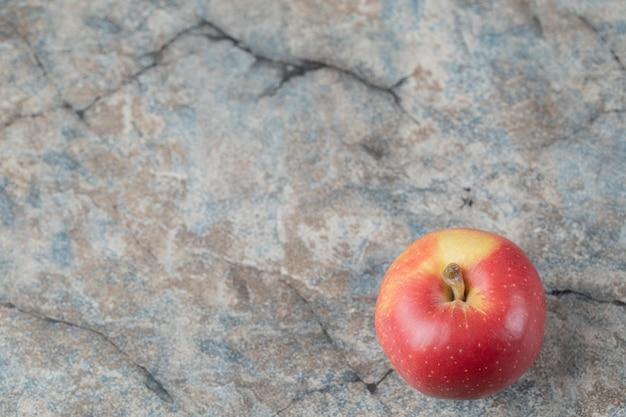 Czerwone jabłko na białym tle na teksturowanej powierzchni