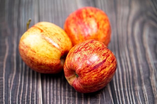 Czerwone jabłko na drewnianym tle
