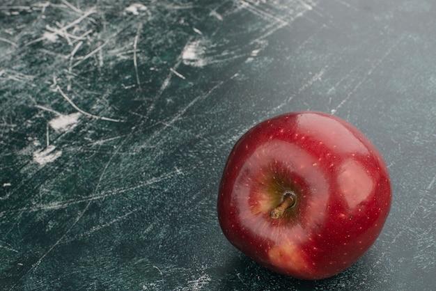 Czerwone jabłko na marmurowej ścianie.