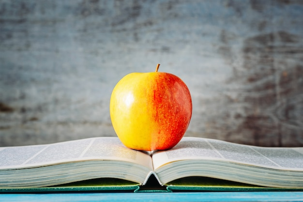 Czerwone jabłko na otwartej księdze