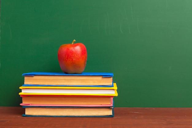 Czerwone jabłko na stosie książek, papieru i ołówka na biurku