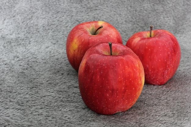 Czerwone jabłko na szarym stole