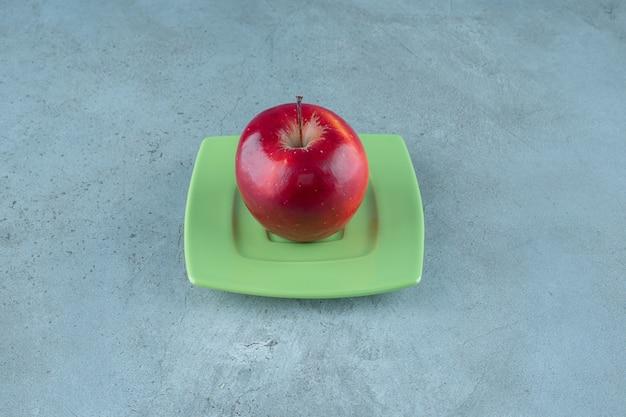 Czerwone jabłko na talerzu, na marmurowym tle. zdjęcie wysokiej jakości