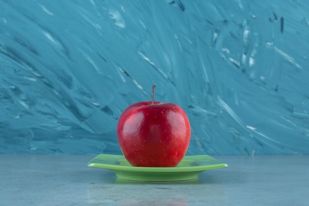 Czerwone jabłko na talerzu, na marmurowym tle.