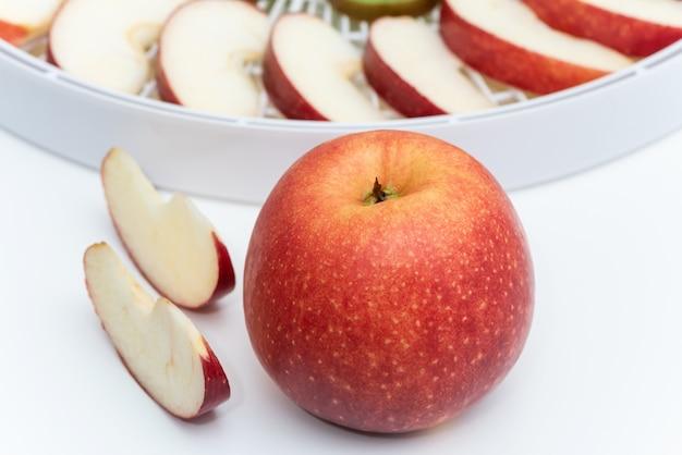 Czerwone jabłko na tle odwadniacza tacy z plasterkami jabłek.