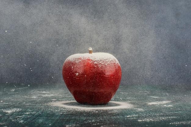 Czerwone jabłko ozdobione proszkiem na niebieskim tle.