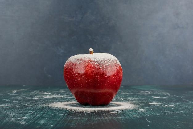 Czerwone jabłko ozdobione pudrem na niebieskim stole.