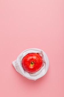Czerwone jabłko w białej sukiennej torbie na różowym tle