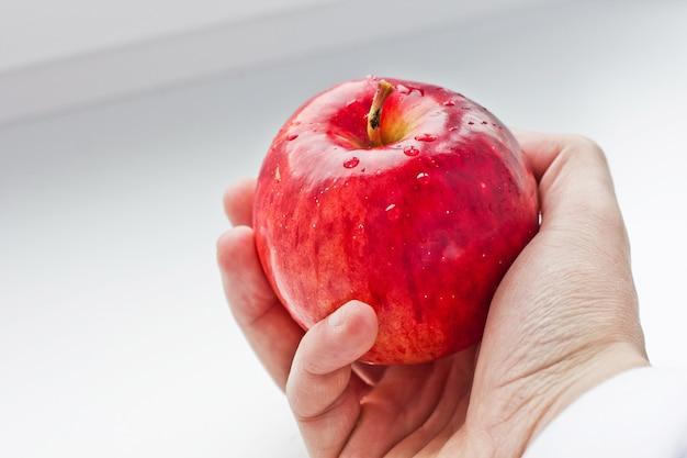 Czerwone jabłko w dłoni