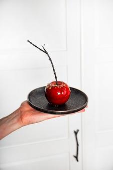 Czerwone jabłko w karmelu z dekoracją cukrową oryginalna uczta na świąteczny stół halloween pionowe zdjęcie