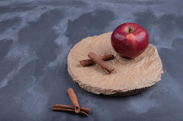 Czerwone jabłko z cynamonem na niebieskiej powierzchni.