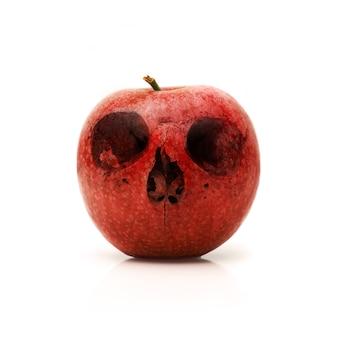 Czerwone jabłko z czaszką rysowane na nim
