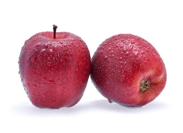 Czerwone jabłko z kroplami wody na białym tle