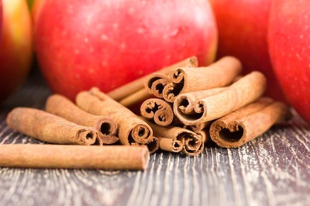 Czerwone jabłko z laskami cynamonu