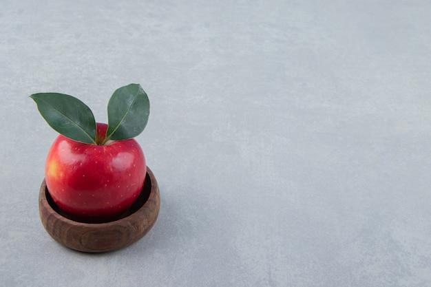 Czerwone jabłko z liśćmi w drewnianej misce.