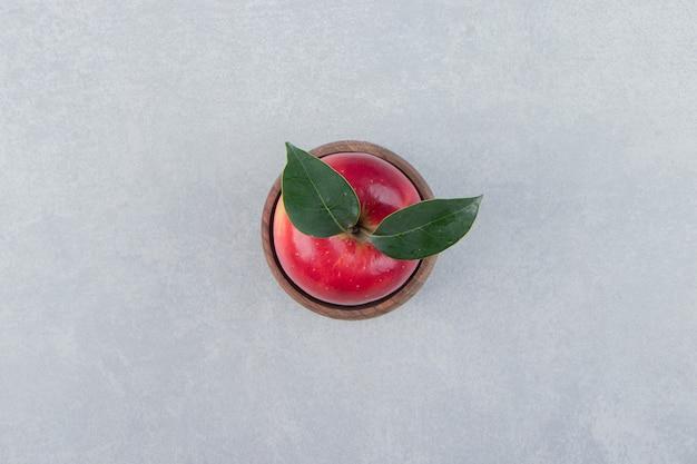Czerwone jabłko z liśćmi w drewnianej misce