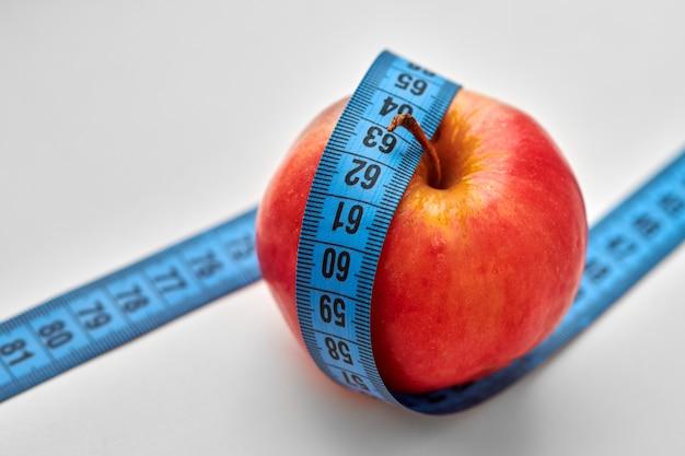Czerwone jabłko z niebieską miarką wokół niego na białym tle. dieta, prawidłowe odżywianie i koncepcja zdrowego stylu życia.