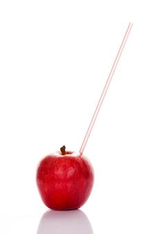 Czerwone jabłko ze słomką na białym tle