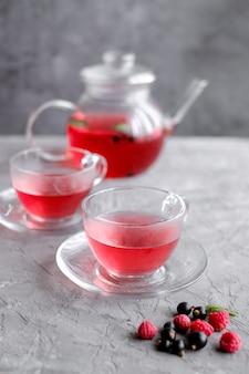 Czerwone jagody herbaty w filiżance i czajniczku