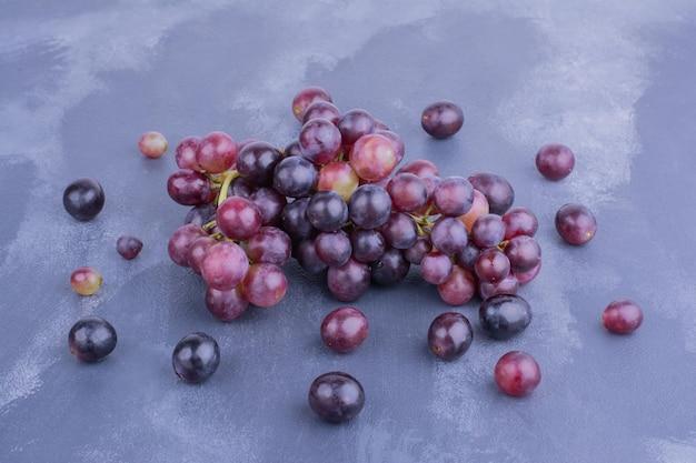 Czerwone jagody winogron na białym tle na niebieskim stole.
