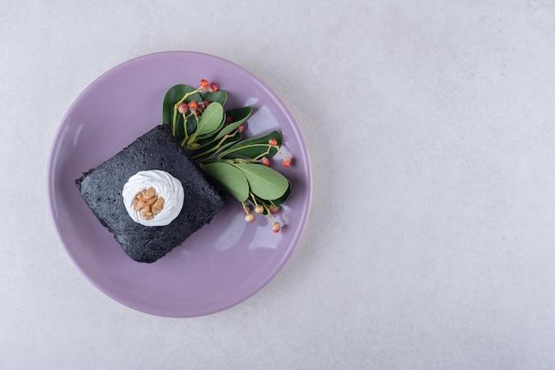 Czerwone jagody z ciastem brownies z orzechami na talerzu, na marmurze.