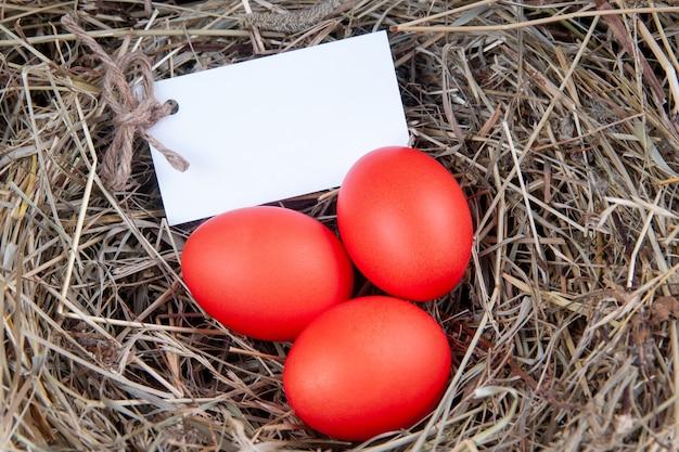 Czerwone jajka z nutą w sianie. makieta, koncepcja wielkanocna.