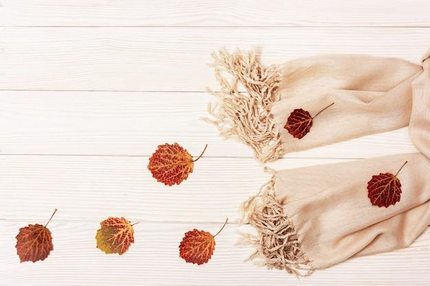 Czerwone jesienne liście z drzewa osiki i szalik z tkaniny
