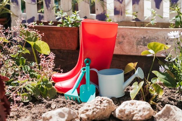 Czerwone kalosze; konewka i narzędzia ogrodnicze w ogrodzie
