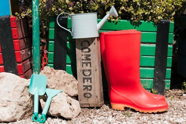 Czerwone kalosze; konewka; narzędzia ogrodnicze w ogrodzie