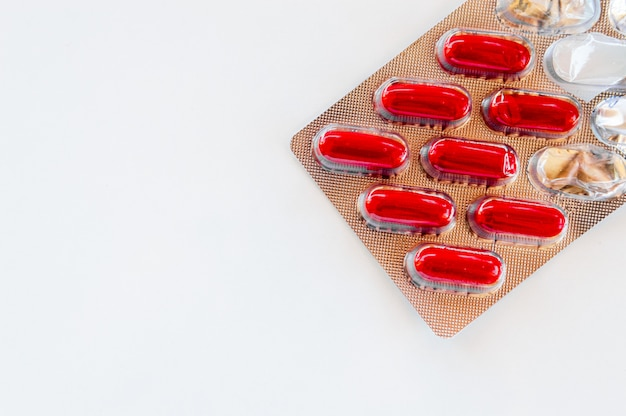 Czerwone kapsułki pakowane w pojedyncze blistry