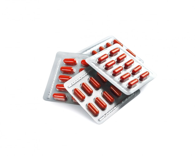 Czerwone kapsułki pigułki w blistrach na białym tle