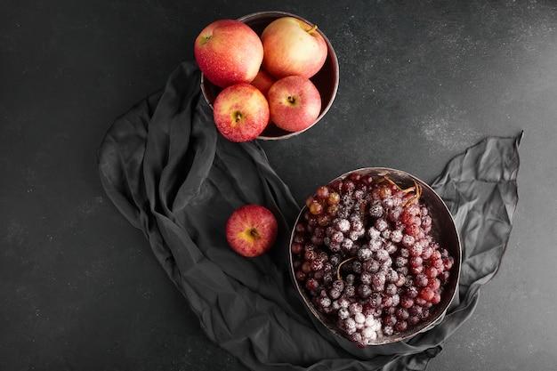 Czerwone kiście winogron i jabłka w metalowych kubkach, widok z góry.