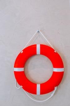 Czerwone koło ratunkowe z białym paskiem zawieszonym na białej ścianie miało po lewej stronie miejsce na kreatywność. bezpieczeństwo na wodzie.