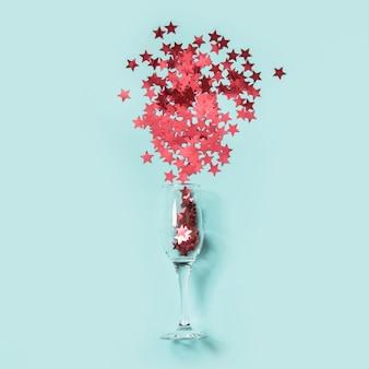 Czerwone konfetti w kształcie gwiazd wylały kieliszki szampana na niebiesko.