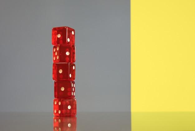 Czerwone kostki na białym tle na nowoczesnym tle szarym i żółtym. koncepcja hazardu.