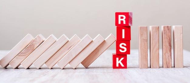 Czerwone kostki ryzyka blokują spadanie bloków na stole. upadek koncepcje biznesowe, planowania, zarządzania, rozwiązania, ubezpieczenia i strategii