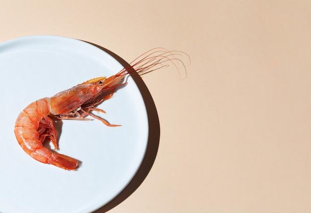 Czerwone krewetki na białym talerzu i beżowym tle. minimalistyczna koncepcja z owocami morza